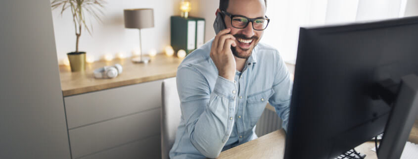 employee smiling, using phone for remote working