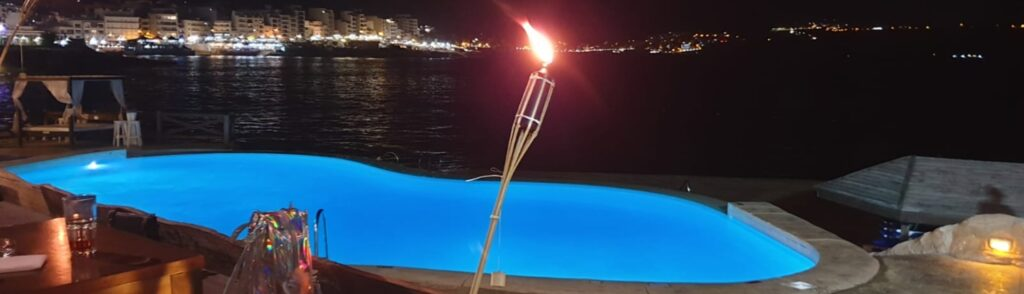 photo of pool at night, lit torch