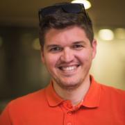 photo of smiling employee in orange shirt