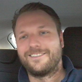 photo of employee smiling, in car