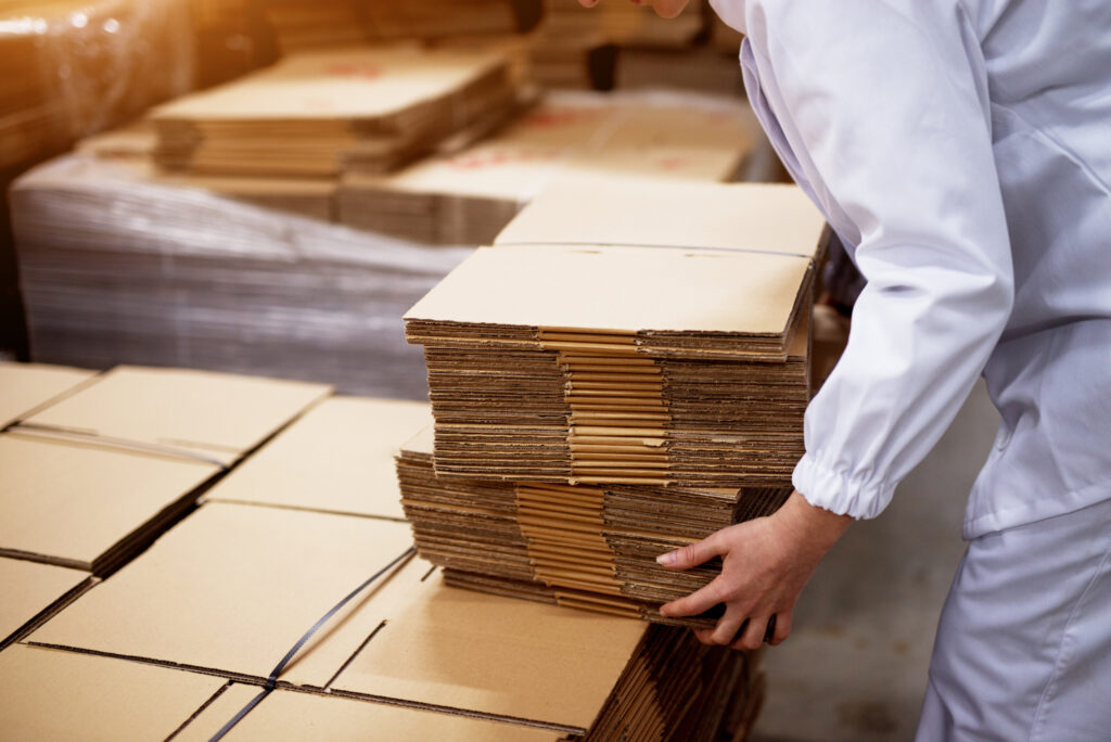 manufacturing employee stacks of folded cardboard boxes